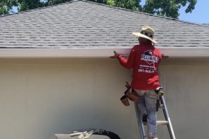 Local Houston Gutter Company installing seamless gutters